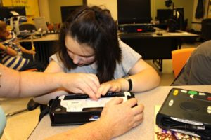 Photo of a student working with braille technology