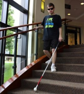 Photo of a student using a white cane while walking down stairs